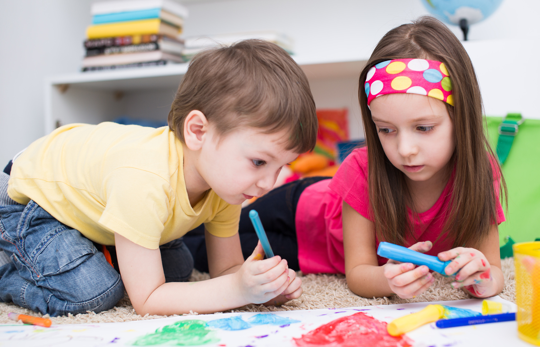 two little kids painting with paintbrush and colorful paints